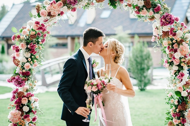 The bride and groom kissing. Newlyweds with a wedding bouquet, holding glasses of champagne standing on wedding ceremony under the arch decorated with flowers and greenery of the outdoor.